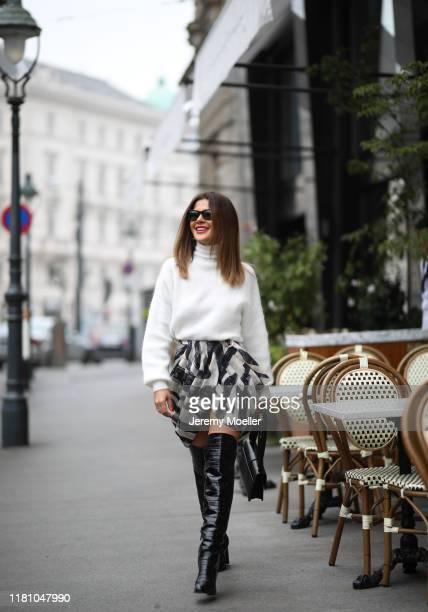 Füsun Lindner wearing Dior bag, H&M skirt, Zara sweater and Max Mara boots on October 13, 2019 in Vienna, Austria.