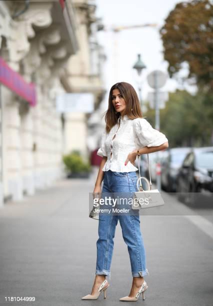 Füsun Lindner wearing Zara blouse, Levis jeans, Dior heels, Florian London bag and Celine sunglasses on October 13, 2019 in Vienna, Austria.