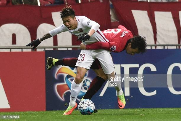 Fu Huan of Shanghai SIPG and Tomoya Ugajin of Urawa Red Diamonds compete for the ball during the AFC Champions League Group F match between Urawa Red...