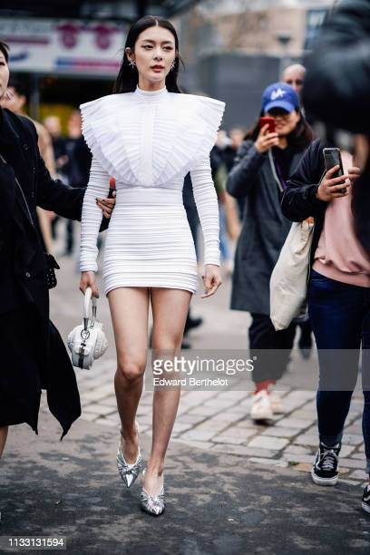 Fu Jing actress and singer from the Chinese band Rocket Girls 101 wears star shaped earrings a white ruffled dress outside Balmain during Paris...