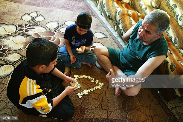 Fuad Mosa Muhammad age 40 plays domino with his sons Ahmed and Muhammad at his house on March 28 2007 in Baghdad Iraq Fuad a cook at a breakfast and...
