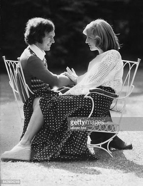 Fußballspieler Franz Beckenbauer und seine Frau Brigitte sitzen sich Hände haltend auf Gartenstühlen gegenüber Aufgenommen 1974