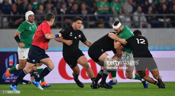 Fuchu , Japan - 19 October 2019; Robbie Henshaw of Ireland loses possession in a tackle by Sam Cane and Anton Lienert-Brown of New Zealand during the...