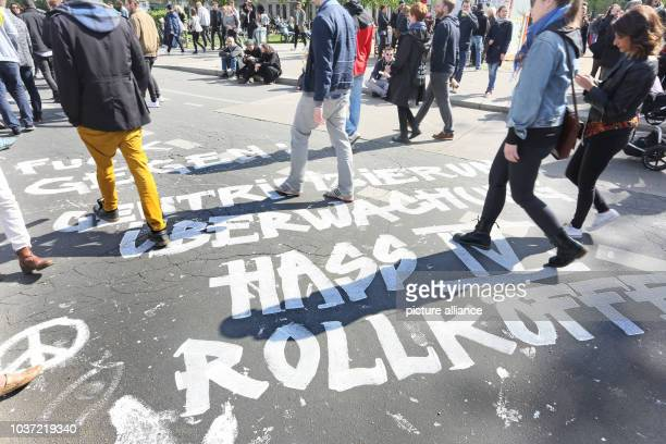 'Fuck against gentrification surveillance hate IV rolling suitcases'can be read on the pavement amongst guests at the 'MyFest' May Day celebrations...