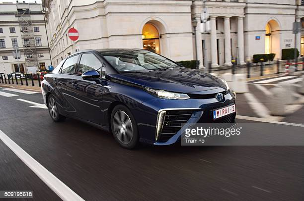 fuel cell vehicle driving on the street - toyota motor co stock pictures, royalty-free photos & images