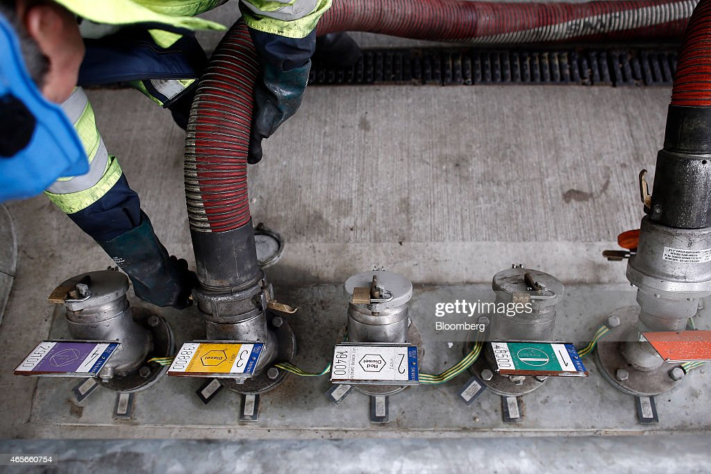 A fuel delivery truck driver attaches a hose to a storage tank