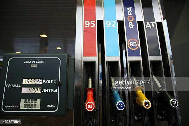Fuel dispensing nozzles sit on a fuel pump beside an electronic price indicator on the forecourt of an OAO Rosneft gas station in Moscow Russia on...