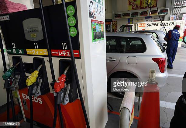 Fuel nozzle guns sit at a gas station as an attendant fills the tank of a vehicle in Tokyo Japan on Friday Aug 30 2013 Japan's consumer prices...