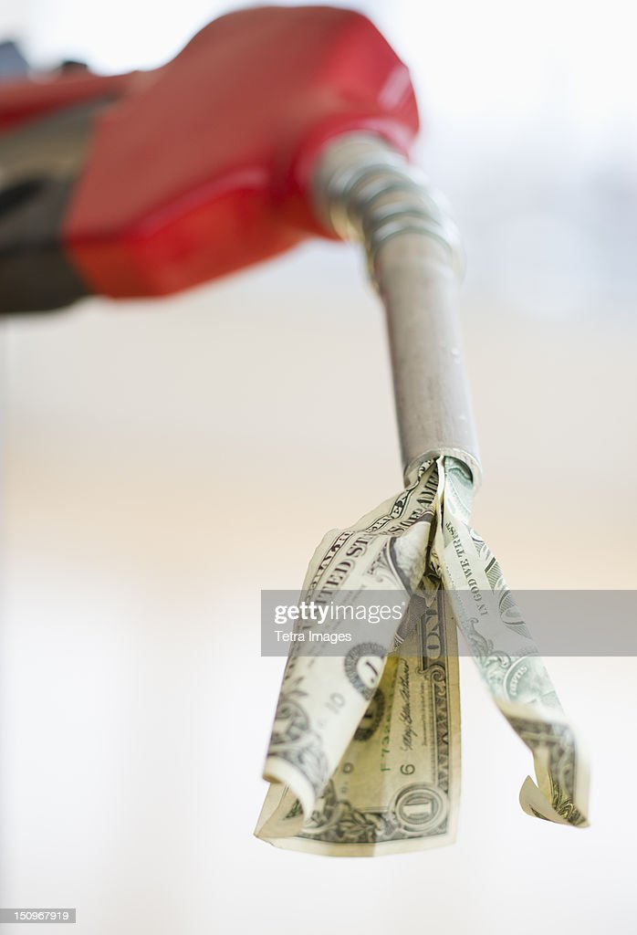 Fuel nozzle with dollar bill : Stock Photo
