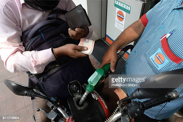 A fuel pump employee fills a car with petrol at a service station in New Delhi on September 29 2016 / AFP / PRAKASH SINGH