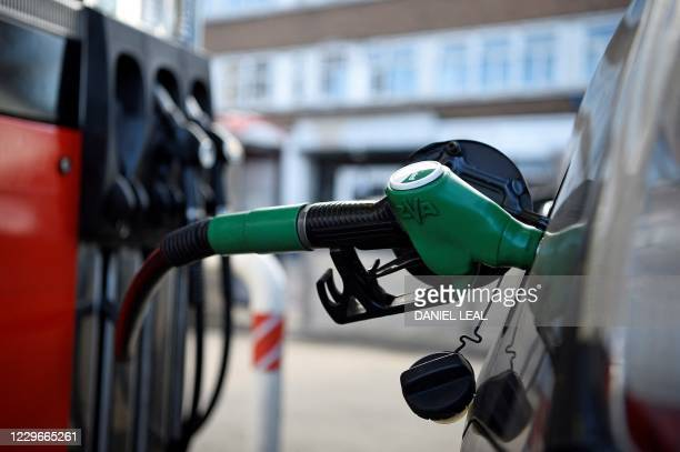 Fuel pump is pictured as it refuels a car with unleaded petrol at a petrol station in north London on November 18, 2020. - Britain will ban petrol...