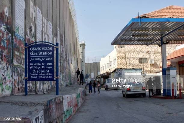 A fuel station seen next to the Separation Wall The Israeli Separation Wall is a dividing barrier that separates the West Bank from Israel