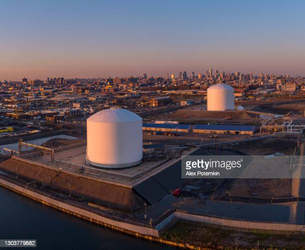 fuel storage tanks in the industrial zone in east williamsburg, brooklyn, new york, with the remote view of downtown manhattan in the backdrop. vertical stitched panorama. - brooklyn new york stock pictures, royalty-free photos & images