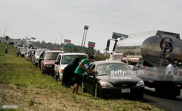 A fuel supplier employee fills up an evacuee's empty car as others wait on Interstate 45 North September 23 2005 just north of Houston Texas...