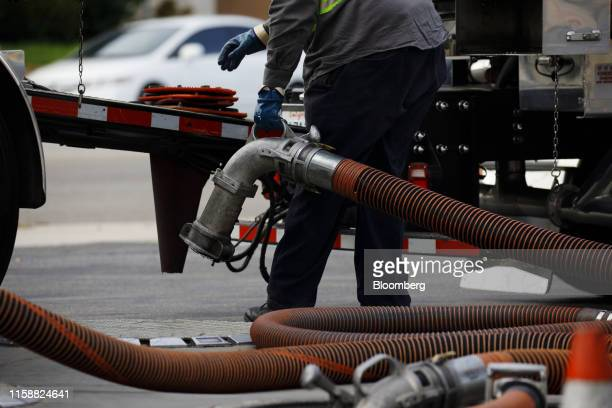 A fuel tanker truck driver disconnects a hose after delivering gasoline at a Royal Dutch Shell Plc gas station in Redondo Beach California US on...