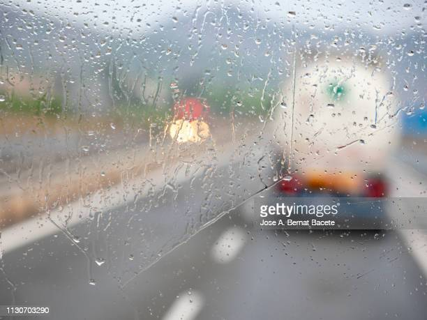 fuel truck circulating on a road with rain. - dashboard camera point of view stock photos and pictures