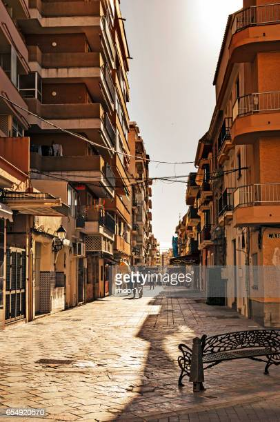 fuengirola spain men and women walking by apartments - fuengirola stock photos and pictures