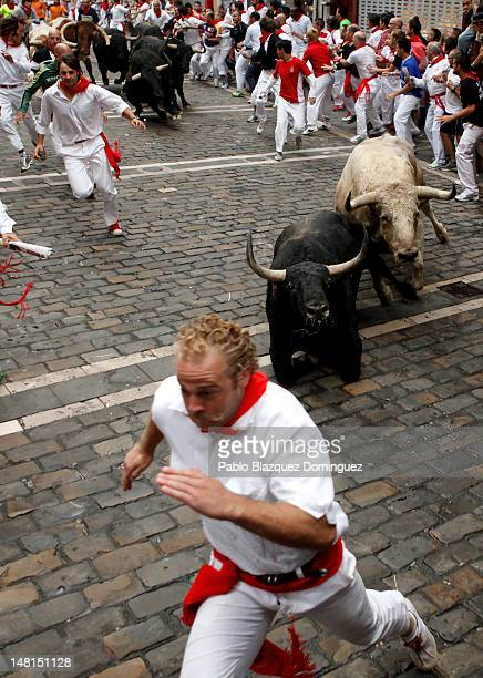 Fuente Ymbro fighting bulls fall running behind of a particiapnt at Curva Estafeta on the sixth day of the San Fermin runningofthebulls on July 11...