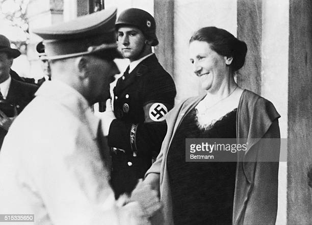 Fuhrer Adolf Hitler greets Frau Winifred Wagner daughterinlaw of the great composer as he arrives at Bayreuth to attend the annual musical festival...