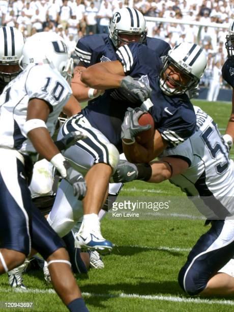 Fui Vakapuna BYU running back breaks the tackle of Utah State defender Ben Calderwood and Kejon Murphy as he scored on an 8-yard touchdownat LaVell...