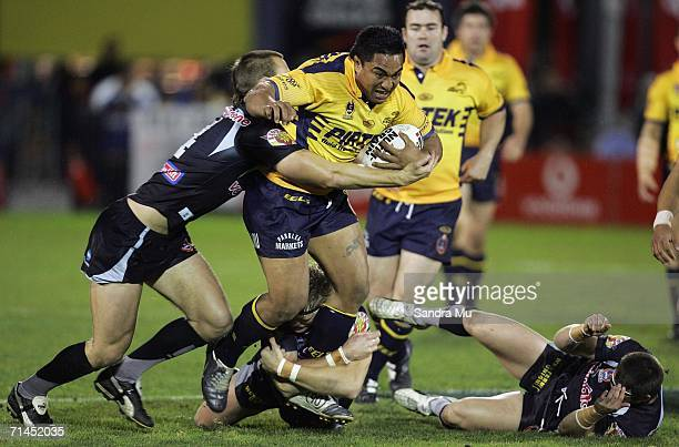 Fuifui Moi Moi of the Eels breaks through the tackle from Simon Mannering and Michael Luck of the Warriors during the round 19 NRL match between the...