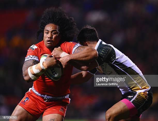 Fuifui Moimoi of Tonga powers his way past Isaac John of Cook Islands during the Rugby League World Cup GroupC/D match between Tonga and Cook Islands...