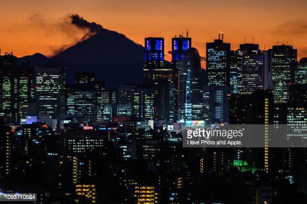 fuji distant view from tokyo at dusk - 東京都庁舎 ストックフォトと画像