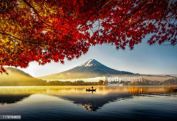 fuji mountain and fisherman boat with morning mist in autumn, kawaguchiko lake, japan - japan stockfoto's en -beelden