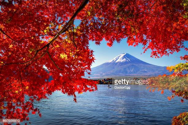 Fuji Mountain and Red Maple Branches with Fisherman Boat at Kawaguchiko Lake in Autumn