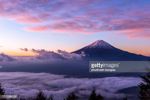 fuji mountain and the mist over lake kawaguchiko at beautiful sunrise , yamanashi, japan, mount fuji or fujisan located on honshu island, is the highest mountain in japan. - mt. fuji stock pictures, royalty-free photos & images