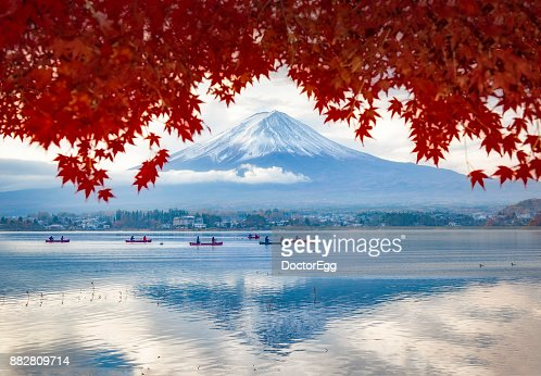 Fuji Mountain in Maple Trees Frame and Tourist Boat with Morning Mist at Kawaguchiko lake in Autumn,Japan