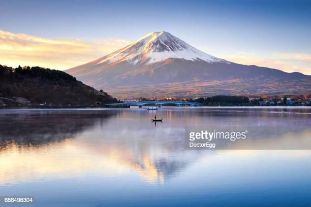 Fuji Mountain Reflection and Fisherman boat in the morning at Kawaguchiko Lake, Japan