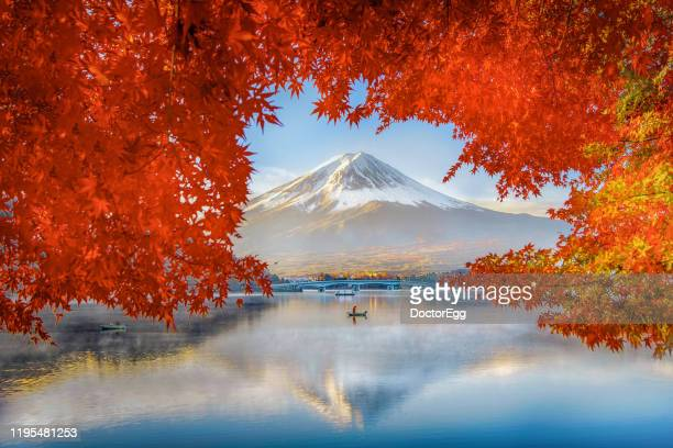 fuji mountain reflection and fisherman boat with red maple leave frame in autumn at kawaguchiko lake, japan - tokyo japan stock pictures, royalty-free photos & images