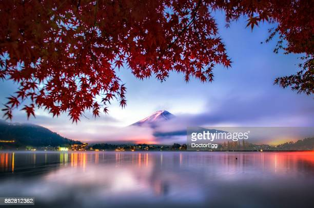Fuji Mountain Reflection and Red Maple Trees with Early Morning Mist at Kawaguchiko lake in Autumn Twilight