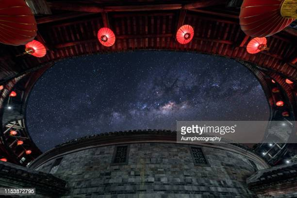 fujian tulou at night with milky way - fujian stock photos and pictures