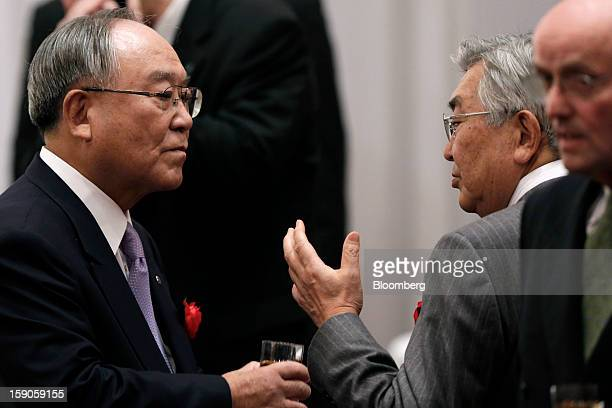 Fujio Mitarai, chairman and chief executive officer of Canon Inc., left, speaks with Atsushi Saito, chief executive officer of Japan Exchange Group...