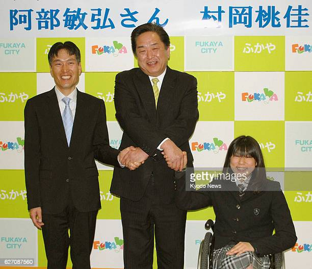 Fukaya Japan Toshihiro Abe and Momoka Muraoka the oldest and youngest athletes on Japan's Sochi Paralympic Games team shake hands with Fukaya Mayor...