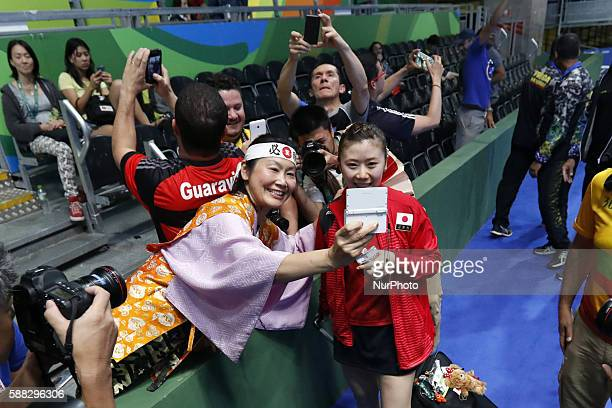 Fukuhara Ai of Japan poses for a photo with a spectator after the women's singles quarterfinal of table tennis between Fukuhara Ai of Japan and Feng...
