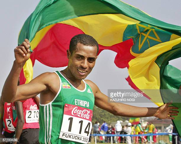 Ethiopia's Kenenisa Bekele holds his national flag as he celebrates his victory in the men's 12kilometre race at the World Cross Country...