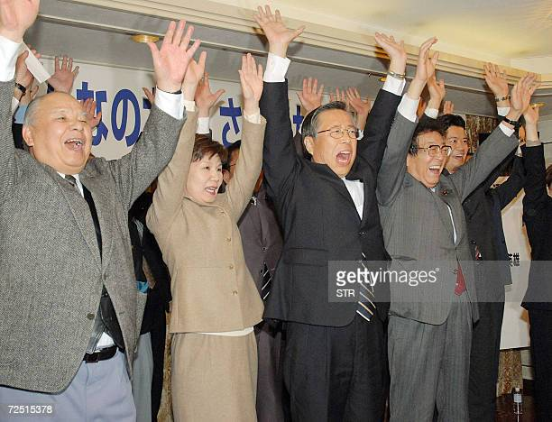 Former parliament member Yuhei Sato supported by Japan's mani opposition Democratic Party of Japan raises his hands for a 'banzai cheer' with his...