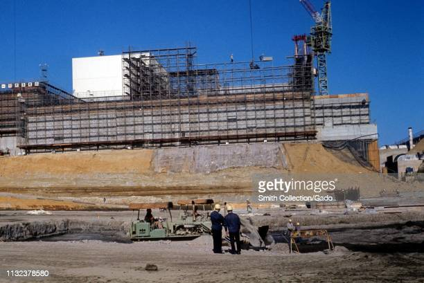 Fukushima Daiichi Nuclear Power Plant, under construction on a sunny day, with workers and machinery in the foreground, Fukushima, Japan, 1970. Image...
