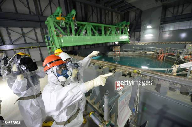 Fukushima Governor Yuhei sato inspects the spent fuel pool in the unit 4 reactor building of Tokyo Electric Power Co Fukushima Daiichi nuclear power...