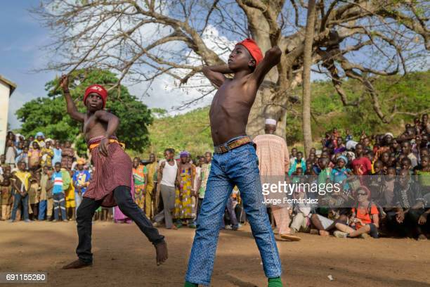Fulani boy hits his opponent with a whip made out of a branch The boy being hit tries his best not to show the pain The crowd around them is watching...