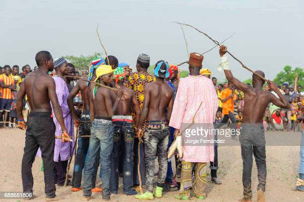 Fulani boys with sticks in their hands waiting in the fighting pit for the combats to start Becoming a man for the Fulani boys of Benin is not an...