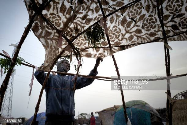 A Fulani displaced man covers his hut with a sheet in the camp for displaced people of Faladie on May 5 2020 On April 28 a fire ravaged the camp...