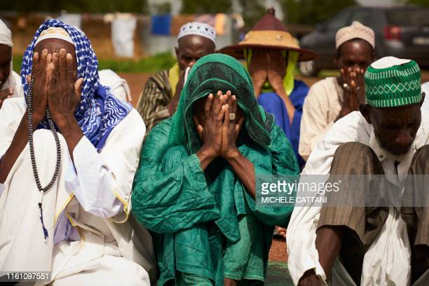 Fulani displaced men cover their faces as they pray during the Eid al-Adha in a refugee camp in Bamako on August 11, 2019. - Muslims across the world...