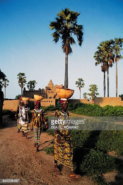 Fulani girls with large bowls on their heads in Massara village Mali
