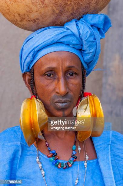 Fulani tribal woman with festive gold earrings and tattooed lips carrying a calabash in Mopti in Mali, West Africa.