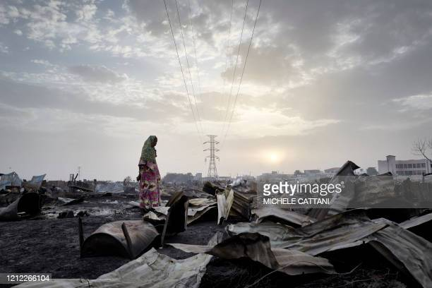 A Fulani woman observes on April 29 2020 the destruction caused by the fire that a day earlier ravaged the camp for displaced people of Faladie A...