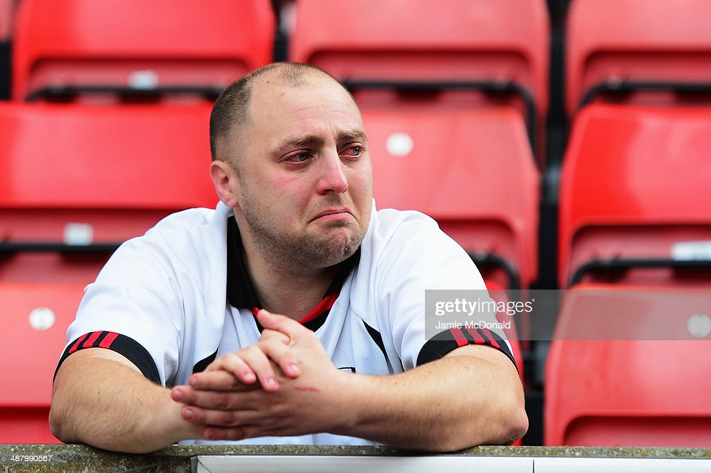 A Fulham fan reacts as his side are relegated following their defeat in the Barclays Premier League match between Stoke City and Fulham at the Britannia Stadium on May 3, 2014 in Stoke on Trent, England.